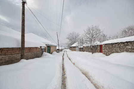 Winter mountain village landscape with snow and cute little houses, beautiful nature of Azerbaijan