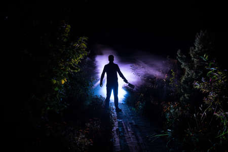 Silhouette of killer with knife standing in the dark forest with light. Horror halloween concept. strange silhouette in a dark spooky forest at night Imagens