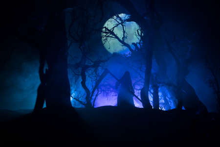 Death with a scythe in the dark misty forest. Woman horror ghost holding reaper in forest, halloween concept. Creative artwork table decorations in selective focus