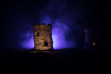 Stone defense tower at night. Medieval castle miniature with toned foggy backlight. Creative table decoration. Selective focus
