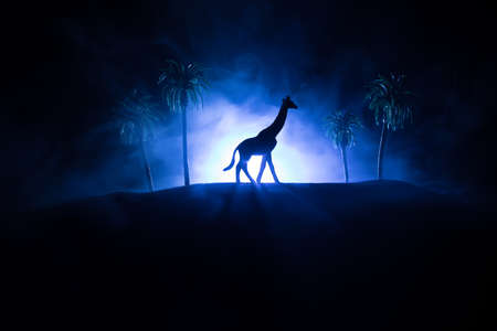 Silhouette of a giraffe miniature standing at foggy night. Creative table decoration with colorful backlight with fog. Selective focus