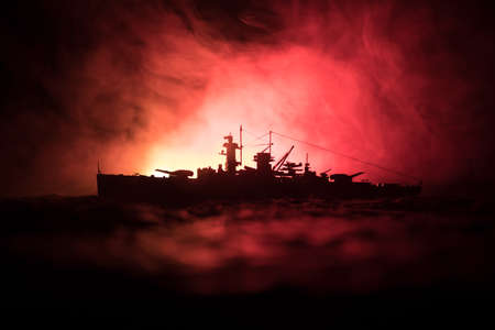 War concept. Night battle scene at sea. Dramatic toned clouds effect. Silhouette of the battle ship in night. Miniature creative table decoration. Selective focus