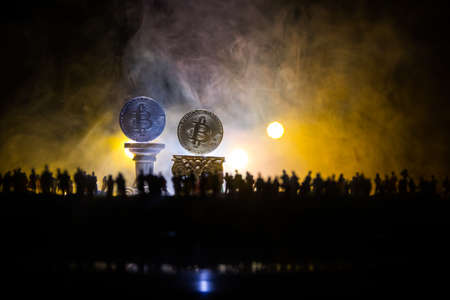 Golden Bitcoin on dark backround. New virtual money. Crypto currency. Crowd miniature looking on Bitcoin in Selective focus Imagens