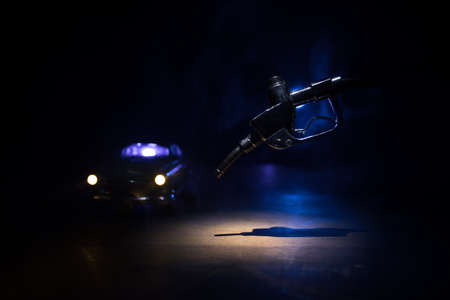 Creative concept. Silhouette of gasoline pistol miniature on dark toned foggy background. Close up. Car miniature on background. Selective focus Stock Photo