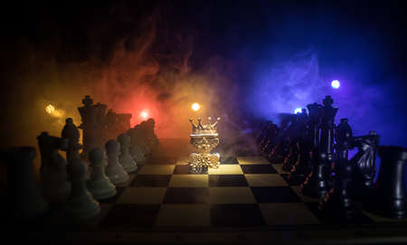Beautiful queen / king crown on chessboard. chess board game concept of business ideas and competition and strategy ideas concept. Chess figures on a dark background with smoke and fog. Selective focus