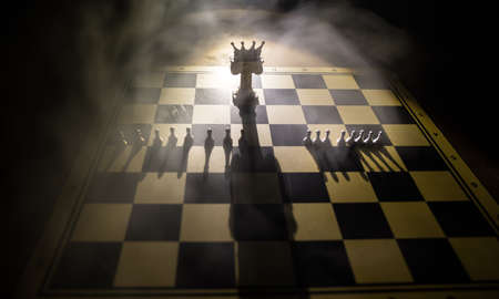 Beautiful crown miniature on chessboard. chess board game concept of business ideas and competition and strategy ideas concept. Chess figures on a dark background with smoke and fog. Selective focus Stockfoto