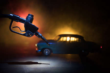 Creative concept. Silhouette of gasoline pistol miniature on dark toned foggy background. Close up. Car miniature on background. Selective focus