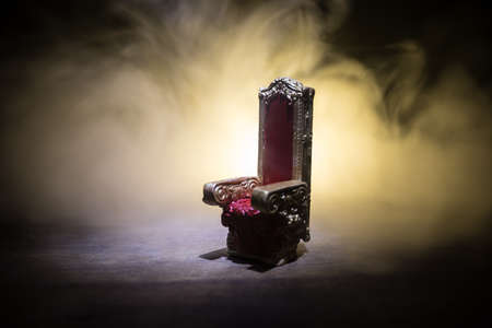 Red royal chair miniature on wooden table. Place for the king. Medieval Throne. Selective focus Stockfoto