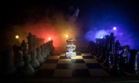 Beautiful queen / king crown on chessboard. chess board game concept of business ideas and competition and strategy ideas concept. Chess figures on a dark background with smoke and fog. Selective focus Imagens