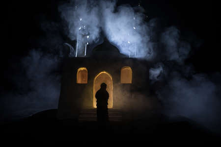 Silhouette of mosque building on toned foggy background. Ramadan Kareem background. Realistic mosque miniature with muslim woman silhouette. Selective focus Фото со стока