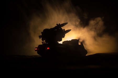 War concept. Battle scene with rocket launcher aimed at gloomy sky at night. Rocket vehicle ready to attack on cloudy war Background. Selective focus Фото со стока