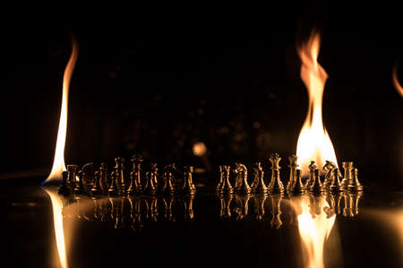? hess pieces on the chessboard against the background of a burning fire. Selective focus Фото со стока