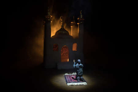 Silhouette of mosque building on toned foggy background. Ramadan Kareem background. Realistic mosque miniature with prayer silhouette. Selective focus Фото со стока