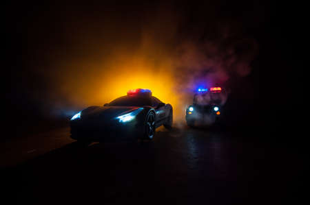 Police car chasing a car at night with fog background. 911 Emergency response police car speeding to scene of crime. Creative decoration. Selective focus Фото со стока