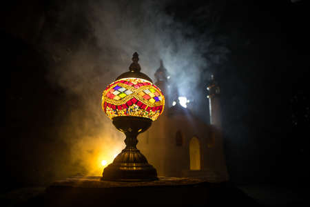 Ornamental Arabic lantern with burning candle glowing at night. Realistic mosque miniature on background. Festive greeting card, invitation for Muslim holy month Ramadan Kareem. Selective focus Фото со стока