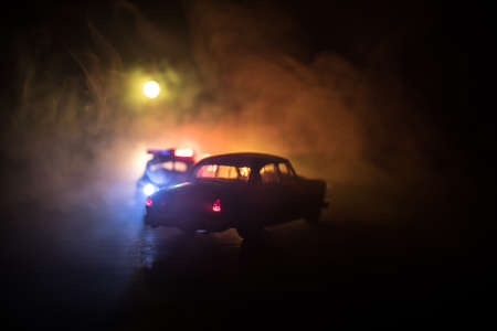 Police car chasing a car at night with fog background. 911 Emergency response police car speeding to scene of crime. Selective focus Stock Photo