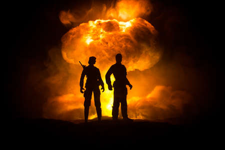 Nuclear war concept. Explosion of nuclear bomb. Creative artwork decoration in dark. Silhouettes of soldiers standing against giant mushroom cloud of atomic explosion. Selective focus