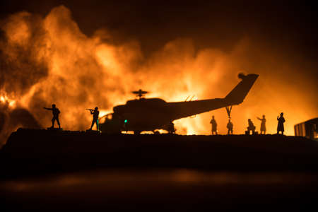 Silhouette of military helicopter ready to fly from conflict zone. Decorated night footage with helicopter starting in desert with foggy toned backlit. Selective focus. War concept 版權商用圖片