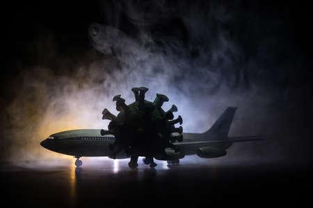 Coronavirus and travel concept. Business and tourism hit by corona virus during pandemic. Artwork decoration. White passenger plane and corona virus miniature in dark. Selective focus 版權商用圖片