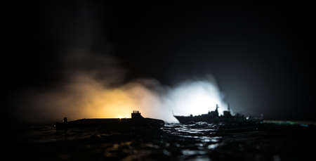 War concept. Night battle scene at sea. Dramatic toned clouds effect. Silhouettes of the battle ship and submarine in night. Miniature creative table decoration. Selective focus