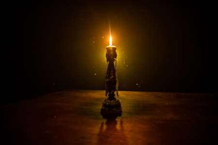 Single burning candle. Light of flame and flowing candle wax, dark background. Selective focus