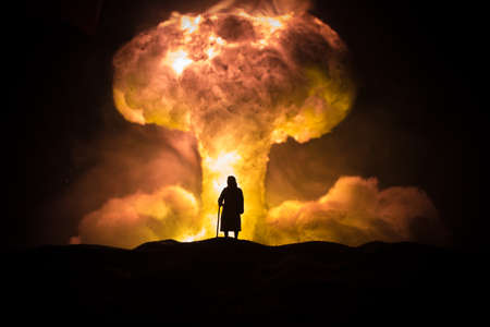 Nuclear war concept. Explosion of nuclear bomb. Creative artwork decoration in dark. Old woman standing against giant mushroom cloud of atomic explosion. Selective focus