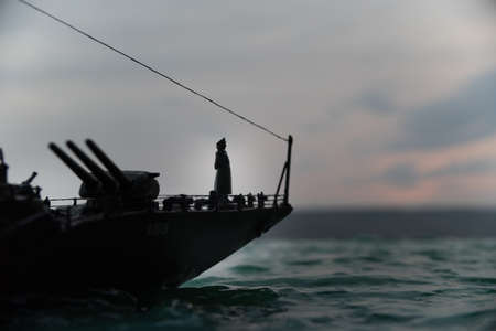 War concept. Night battle scene at sea. Dramatic toned clouds effect. Silhouette of the battle ship at sunset. Miniature creative table decoration. Selective focus