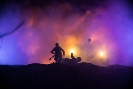 War Concept. Military silhouettes fighting scene on war fog sky background, World War Soldiers Silhouette Below Cloudy Skyline At night. Armored vehicle fight scene. Selective focus Banque d'images