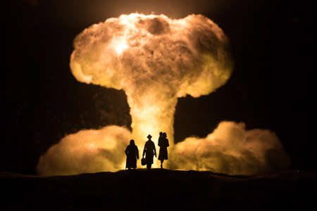 Nuclear war concept. Explosion of nuclear bomb. Creative artwork decoration in dark. Family standing against giant mushroom cloud of atomic explosion. Selective focus