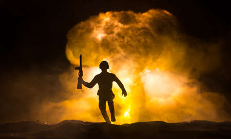 Nuclear war concept. Explosion of nuclear bomb. Creative artwork decoration in dark. Silhouette of soldier trying to escape from atomic explosion. Selective focus