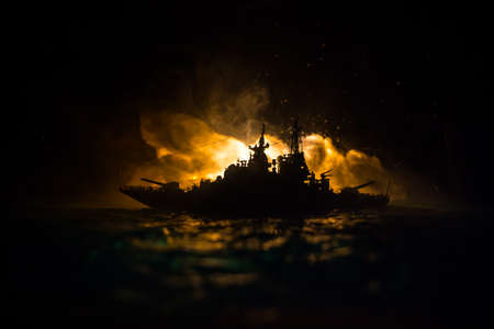 War concept. Night battle scene at sea. Dramatic toned clouds effect. Silhouette of the battle ship in night. Miniature creative table decoration. Selective focus Stock Photo