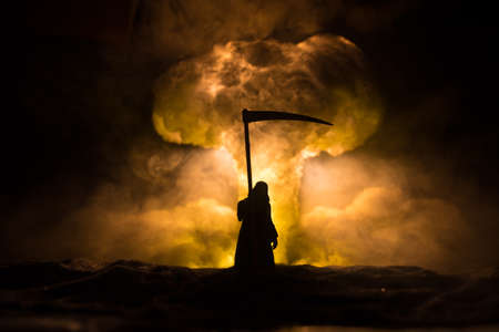 Nuclear war concept. Explosion of nuclear bomb. Creative artwork decoration in dark. Silhouette of grim reaper looking on giant mushroom cloud of atomic explosion. Selective focus