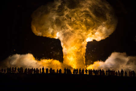 Nuclear war concept. Explosion of nuclear bomb. Creative artwork decoration in dark. People looking on giant mushroom cloud of atomic explosion. Selective focus