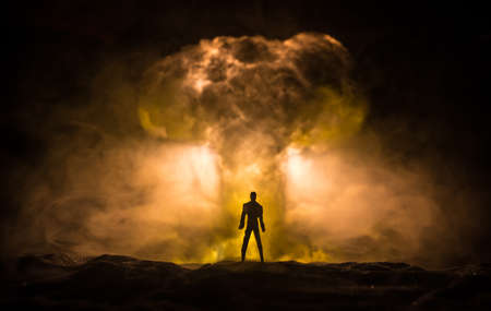 Nuclear war concept. Explosion of nuclear bomb. Creative artwork decoration in dark. Silhouette of a person against giant mushroom cloud of atomic explosion. Selective focus