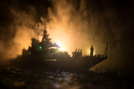 War concept. Night battle scene at sea. Dramatic toned clouds effect. Silhouette of the battle ship in night. Miniature creative table decoration. Selective focus Standard-Bild