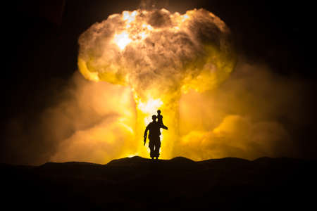 Silhouette soldier carrying little boy on his shoulder from fire. Rescue savior concept. Man moving out with little boy from burned out city destroyed in war. Selective focus Banque d'images
