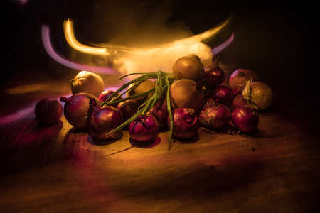 Vegetable concept. Different onions on wood in dark. Selective focus. Colorful background. Archivio Fotografico