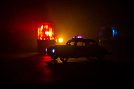 Police car chasing a car at night with fog background. 911 Emergency response police car speeding to scene of crime. Creative decoration. Selective focus Archivio Fotografico