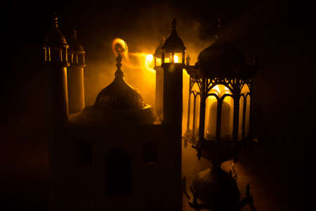 Ornamental Arabic lantern with burning candle glowing at night. Realistic mosque miniature on background. Festive greeting card, invitation for Muslim holy month Ramadan Kareem. Selective focus 免版税图像