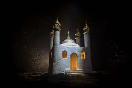 A realistic Mosque miniature with windows at night. Festive greeting card, invitation for Muslim holy month Ramadan Kareem. Selective focus 免版税图像