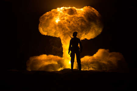 Nuclear war concept. Explosion of nuclear bomb. Creative artwork decoration in dark. Silhouette of soldier standing against giant mushroom cloud of atomic explosion. Selective focus