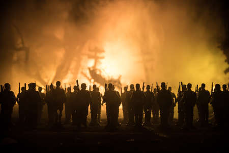 War Concept. Military silhouettes fighting scene on war fog sky background, World War Soldiers Silhouette Below Cloudy Skyline At night. German soldiers in ranks. Selective focus