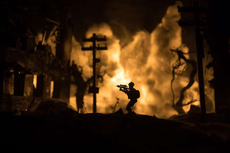 War Concept. Military silhouettes fighting scene on war fog sky background, World War Soldiers Silhouette Below Cloudy Skyline At night. Battle in ruined city. Selective focus