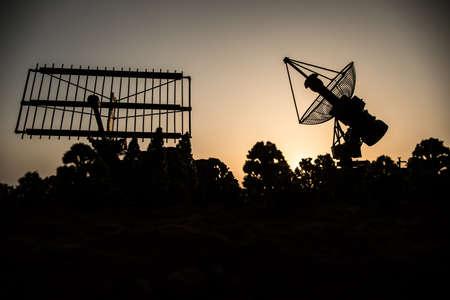 Space radar antenna on sunset. Silhouettes of satellite dishes or radio antennas against night sky. Creative artwork decoration. Selective focus Imagens