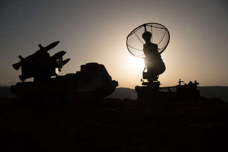 Creative artwork decoration. Silhouette of mobile air defense truck with radar antenna during sunset. Rocket launcher aimed at sky ready to attack. Selective focus Imagens