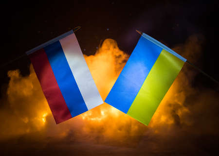 Concept of crisis of war and political conflicts between countries. Russia and Ukraine small flags on dark burning background. Selective focus