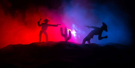 Western concept. Battle between cowboys at night. Duel to the death. Creative artwork decoration on toned foggy background in selective focus Imagens