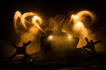 War Concept. Armored vehicle silhouette fighting scene on war foggy sky background at night. American tank ready to fight. Creative decoration Imagens