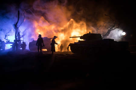 War Concept. Military silhouettes fighting scene on war fog sky background, World War Soldiers Silhouette Below Cloudy Skyline At night. Armored vehicle fight scene. Selective focus