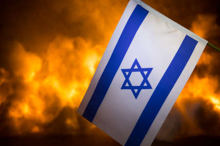 Israel small flag on burning dark background. Concept of crisis of war and political conflicts between nations. Selective focus Imagens